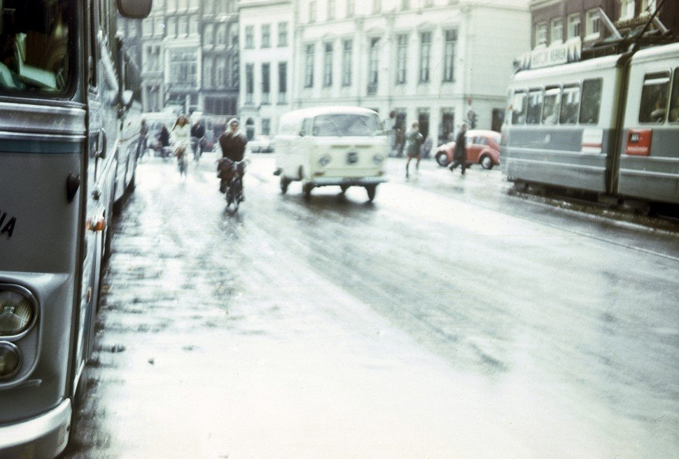 Free image of Rainy street scene with traffic and people, circa 1970.