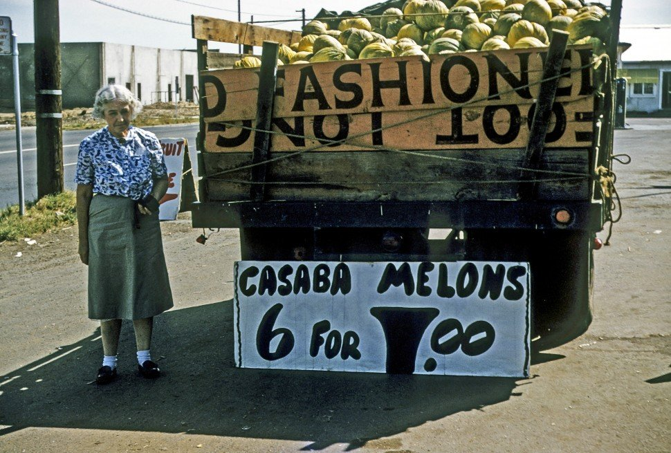 Free image of Elderly woman standing next to a truck load of Casaba Melons.