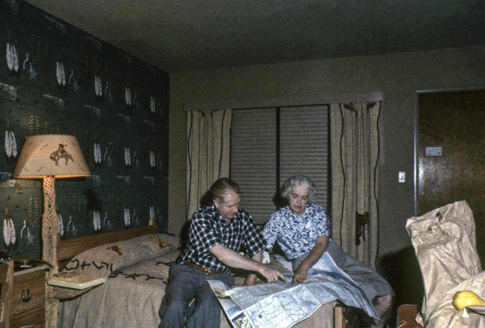 Free image of A couple discussing a road trip in a western themed hotel room.