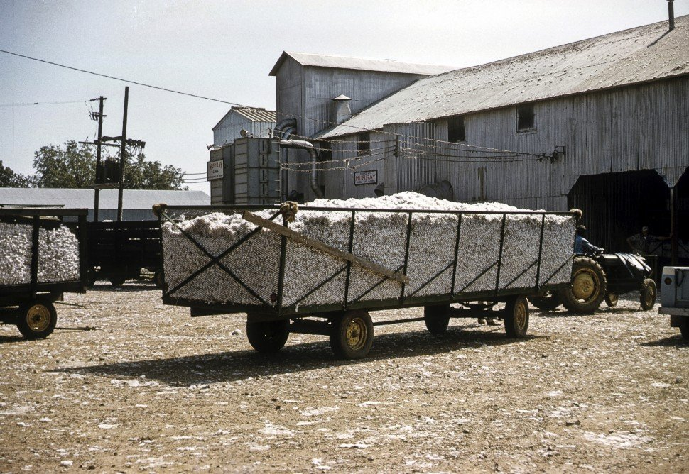 Free image of Cart carrying cotton being pulled into a barn by a tractor.