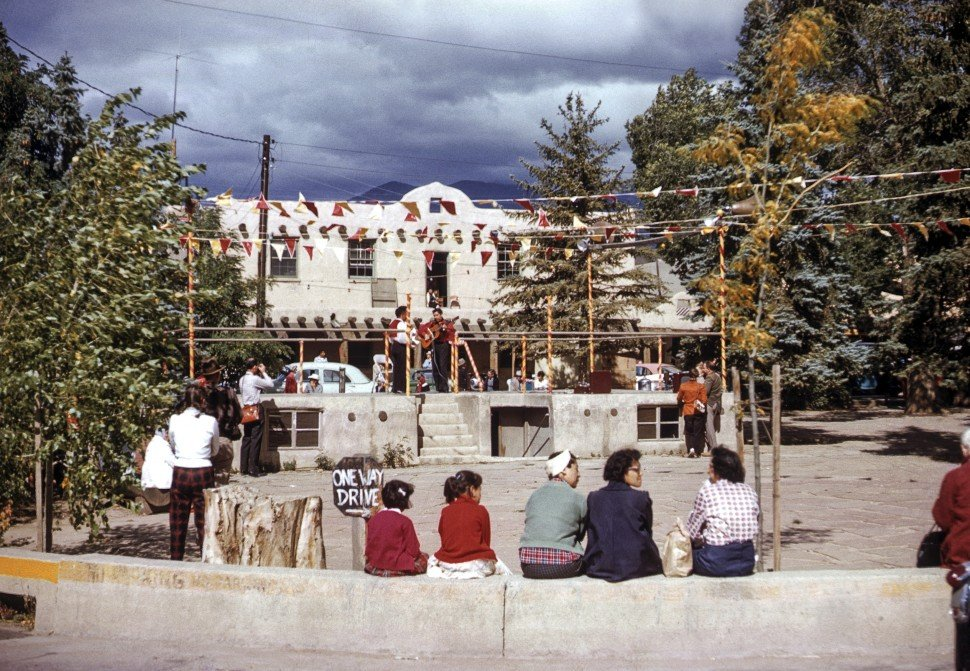 Free image of Group of people watching musicians play in a small plaza in Taos, New Mexico, USA