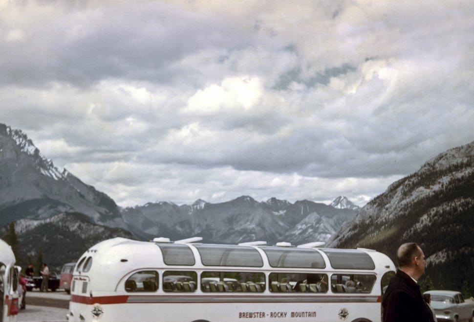 Free image of Tour bus stopped near a mountain range.