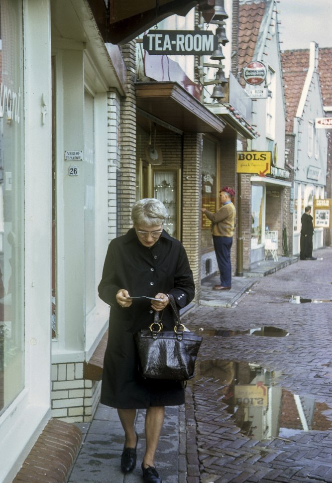 Free image of Woman walking down a rainy cobblestone street while reading.