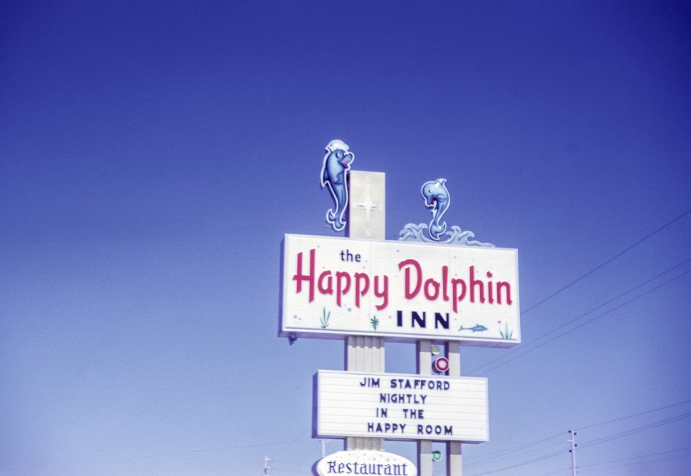 Free image of Sign for the Happy Dolphin Inn against a brilliant blue sky.