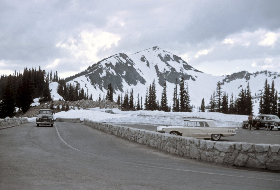 Free image of Car driving down the road in front of snowy mountains and a person standing in a parking lot, circa 1970