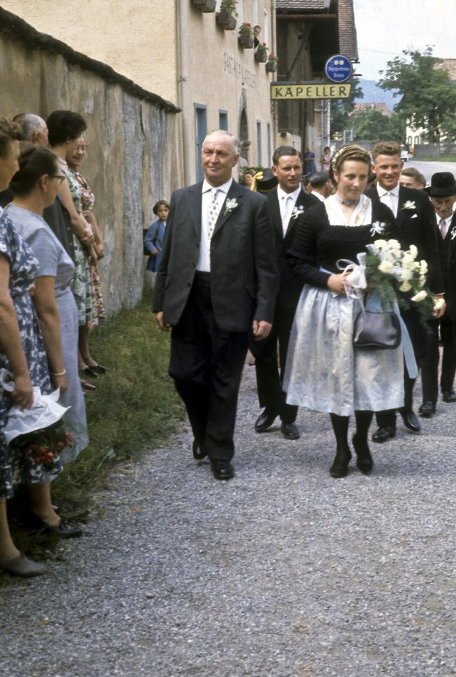 Free image of Wedding party walking down a small street.