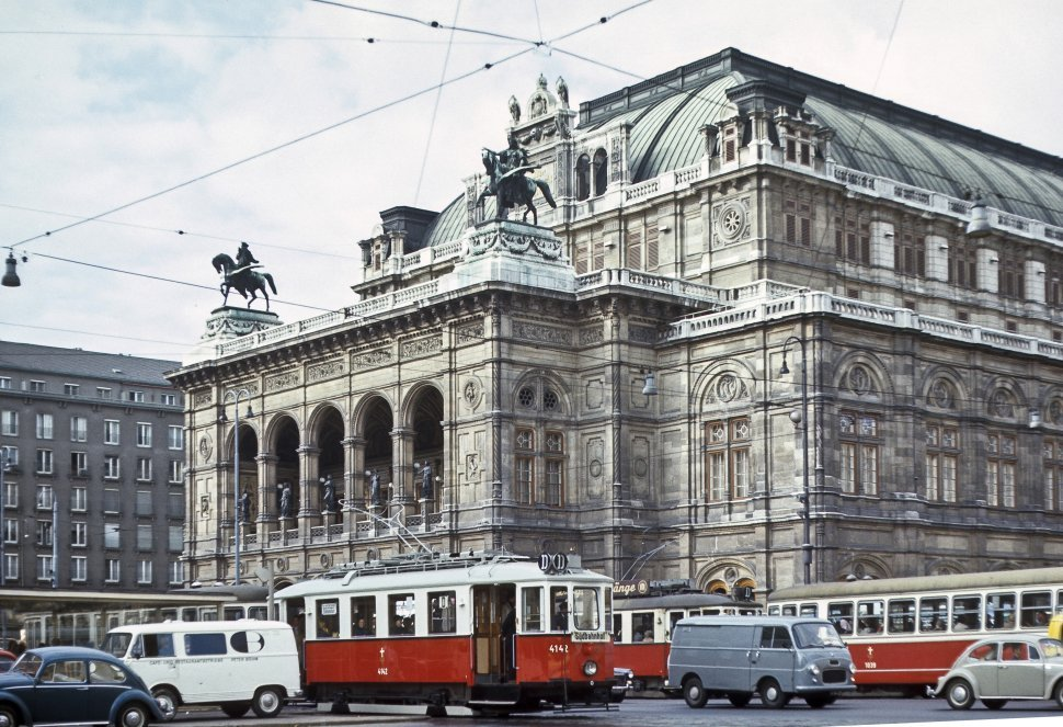 Free image of Traffic and trolley cars driving in front of the Vienna Opera House, circa 1968, Vienna, Austria