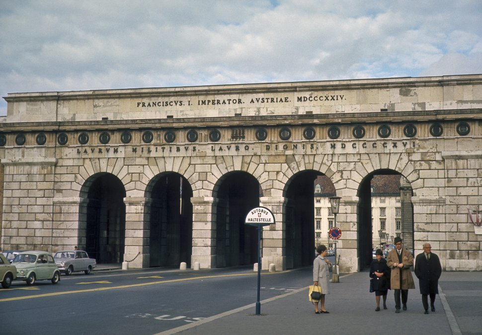 Free image of Four people walking in front of a tunnel, along a sidewalk, circa 1968, Vienna, Austria