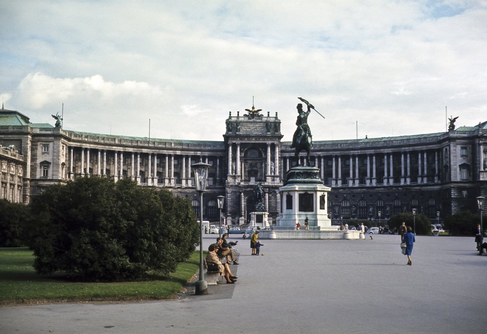 Free image of Group of people walking in front of a large courtyard and statue. Hofburg Palace is the former imperial palace in the centre of Vienna, Austria.