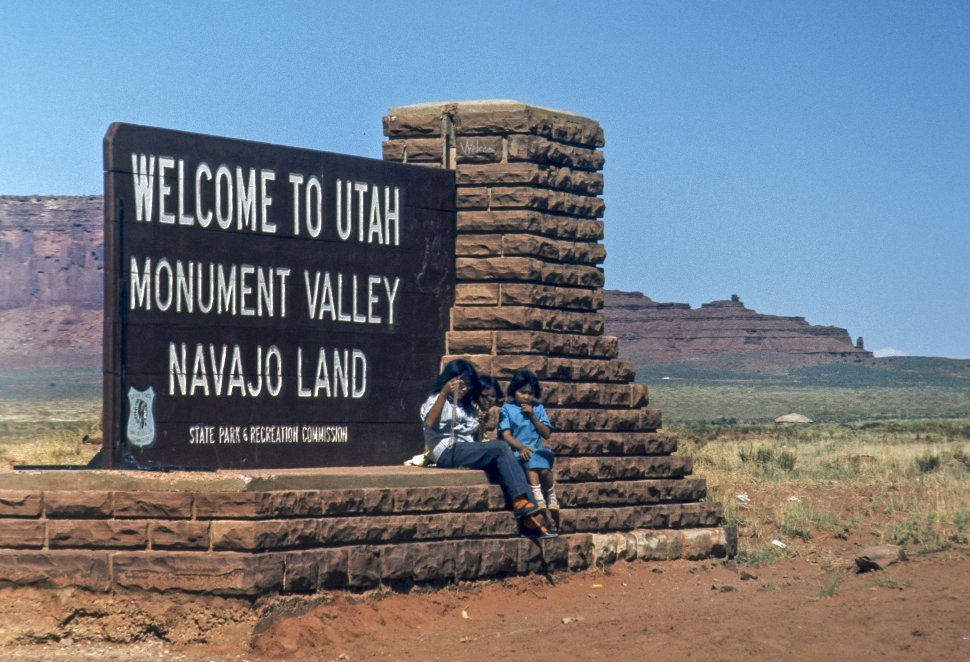 Free image of Three Native American children sitting in front of a sign selling jewelry, circa 1969, Monument Valley, Utah, USA