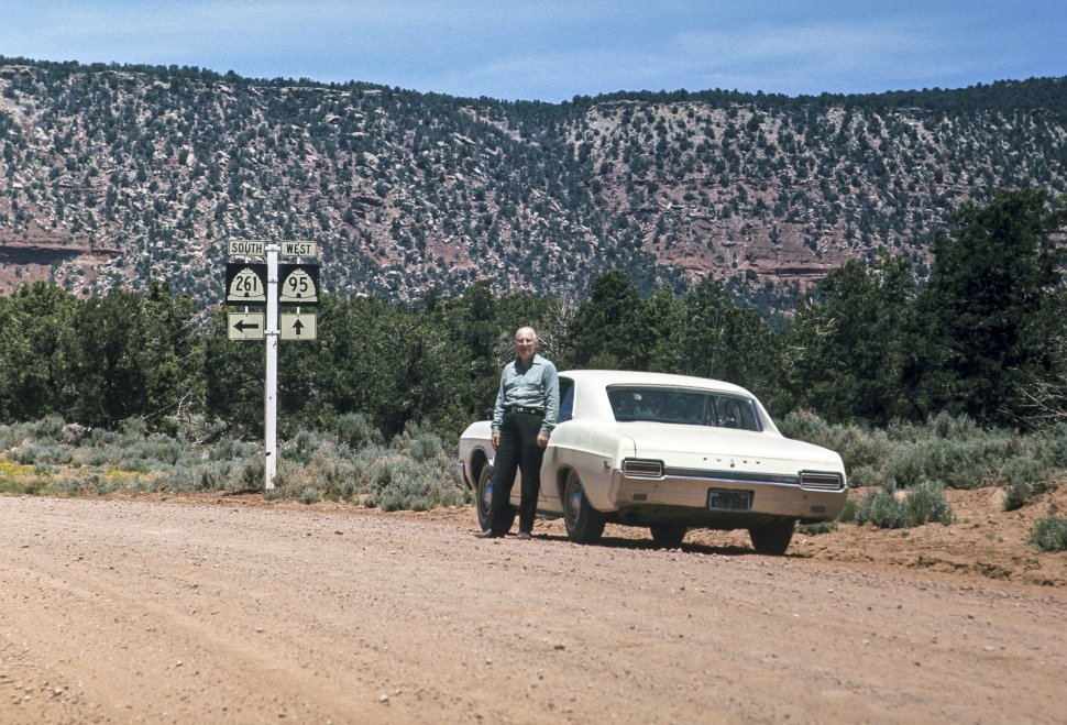 Free image of Elderly man leaning against his car, mesa and road signs in the background, Utah, USA