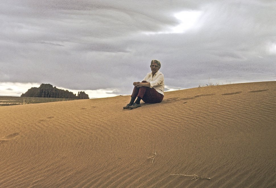 Free image of Older woman sitting on a sand dune, circa 1969, Utah, USA
