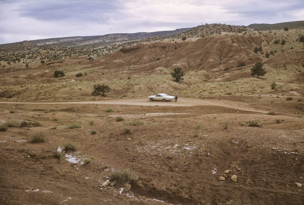 Free image of Person standing next to a car in the distance, circa 1969, Utah, USA