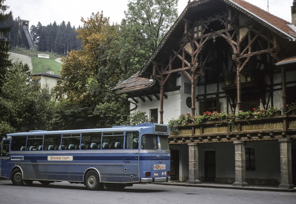 Free image of Tour bus parked in front of a beautiful building.