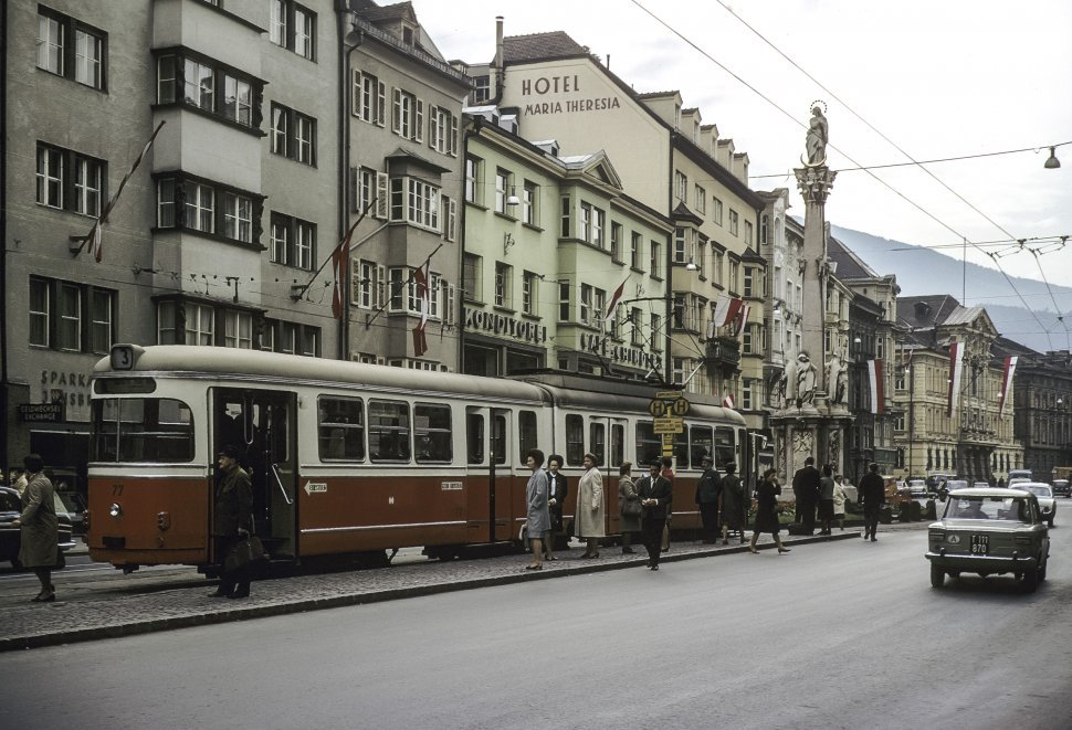 Free image of Group of people standing by a trolley stop and buildings.