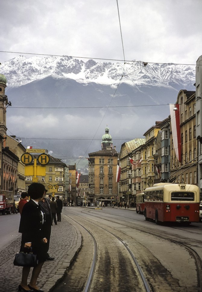 Free image of Woman crossing a city street, with snow capped mountains in the background.