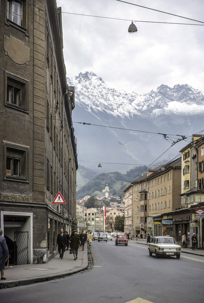 Free image of Group of people walking down a city street with snow capped mountains in the background.