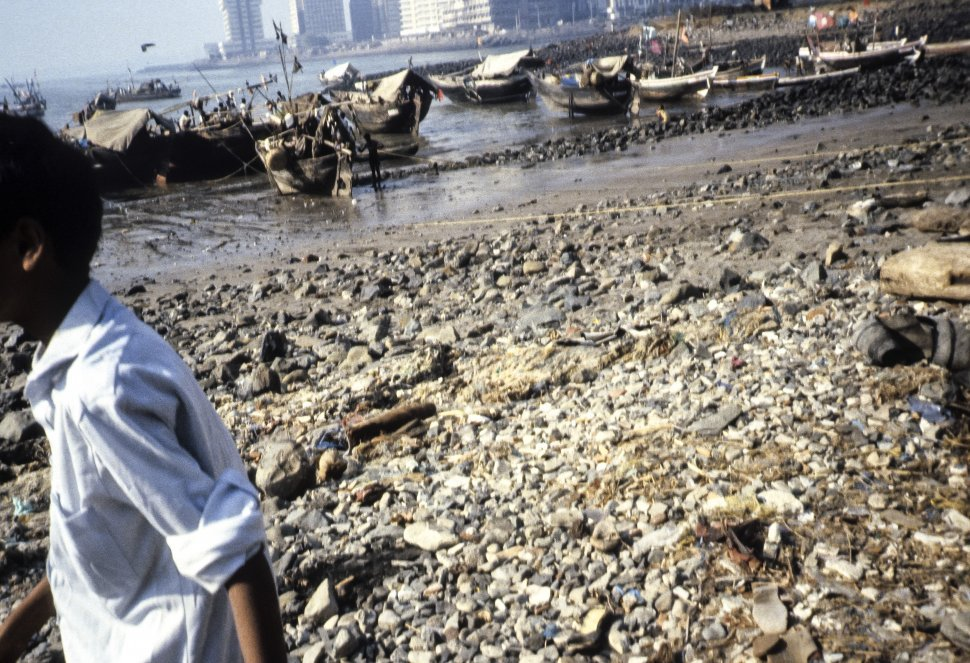 Free image of Child in a white shirt walking in front of a group of fishing boats, India