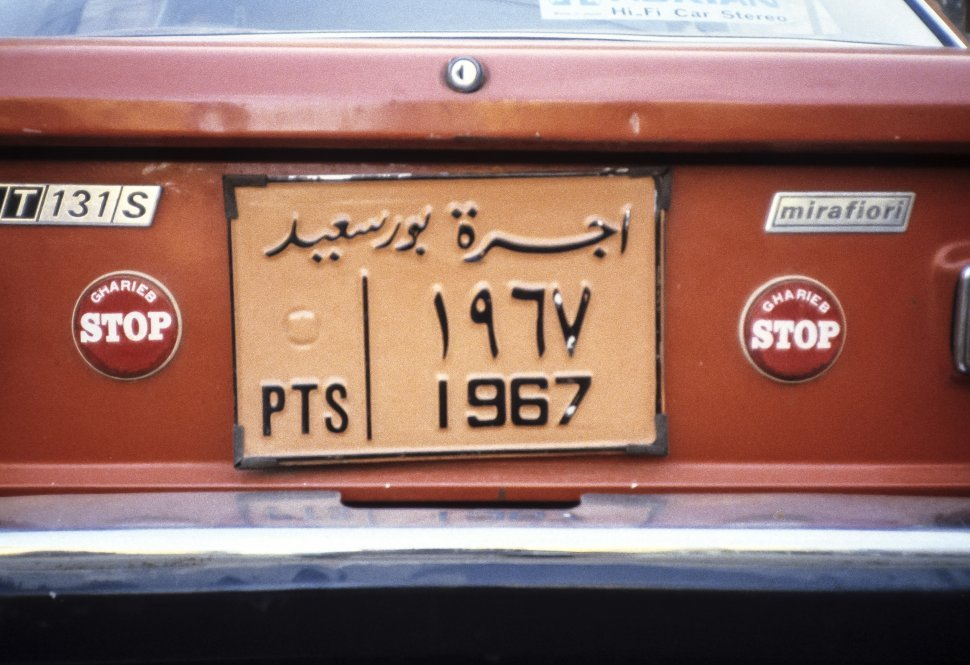 Free image of Close up of a license plate and orange car, India