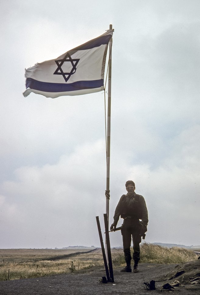 Free image of Soldier standing in front of an Israeli flag, circa 1976, Israel