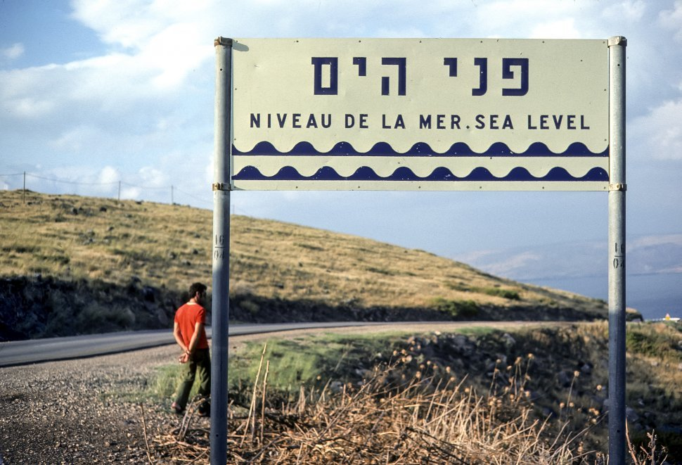 Free image of Man standing in front of a road sign, circa 1976, Israel
