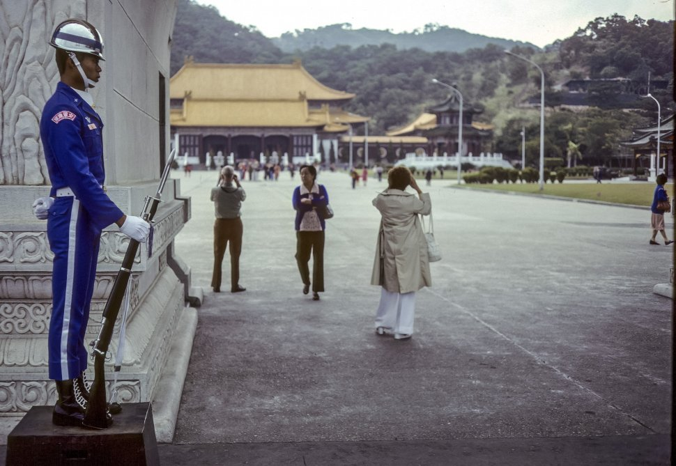 Free image of Tourists taking pictures at a temple with a guard in the foreground, Japan