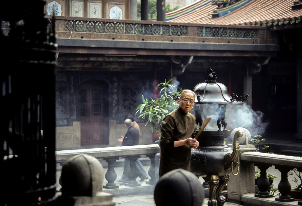 Free image of Japanese priest making a prayer with incense at an altar in a temple, Japan