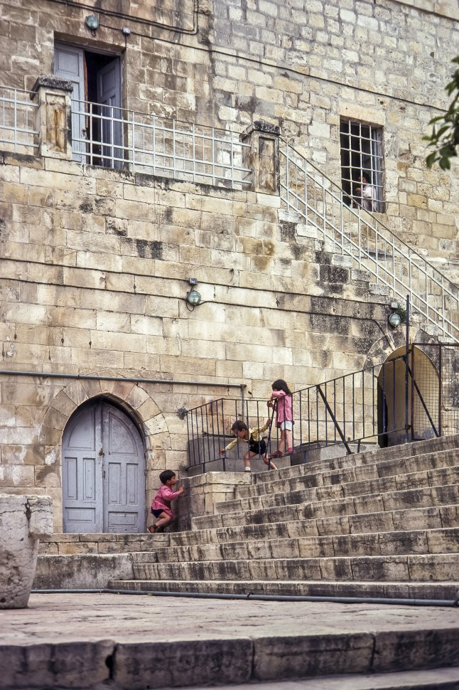 Free image of Three children playing on the stairs of a large brick building, circa 1976, Israel