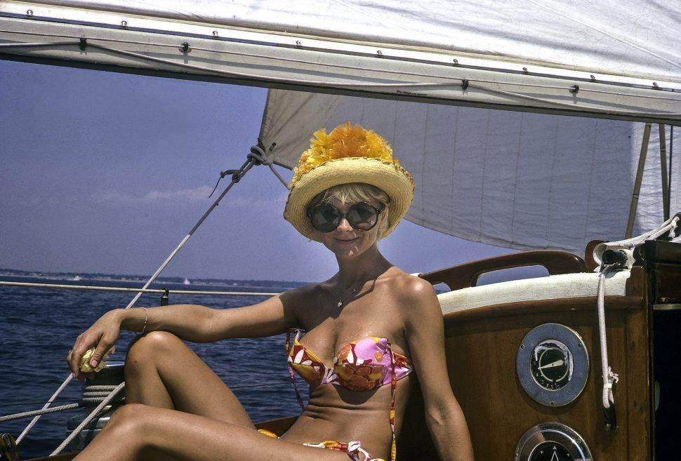 Free image of Woman posing on board a sail boat in a retro style bikini.