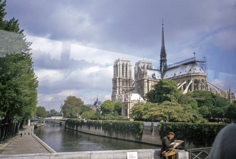 Free image of Photograph, taken from a tour bus, of an artist drawing in front of Notre Dame, Paris, France