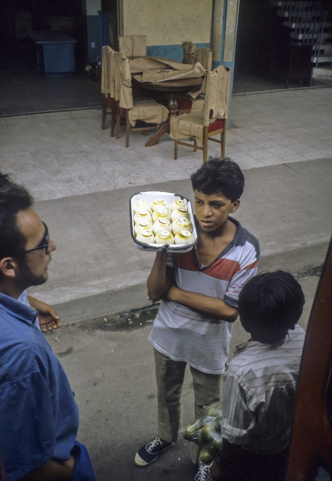 Free image of Child selling beverages to tourists on the street in front of a restaurant.