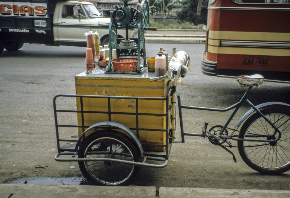 Free image of Beverage cart sitting on the street next to traffic.