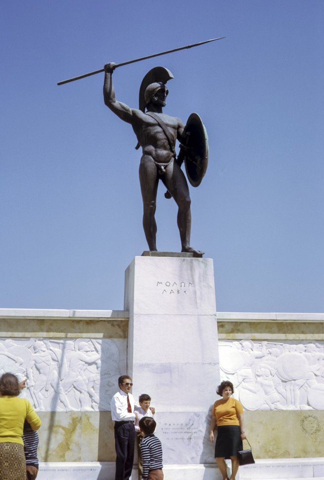 Free image of Tourists standing in front of an ancient bronze statue with a sword and shield.