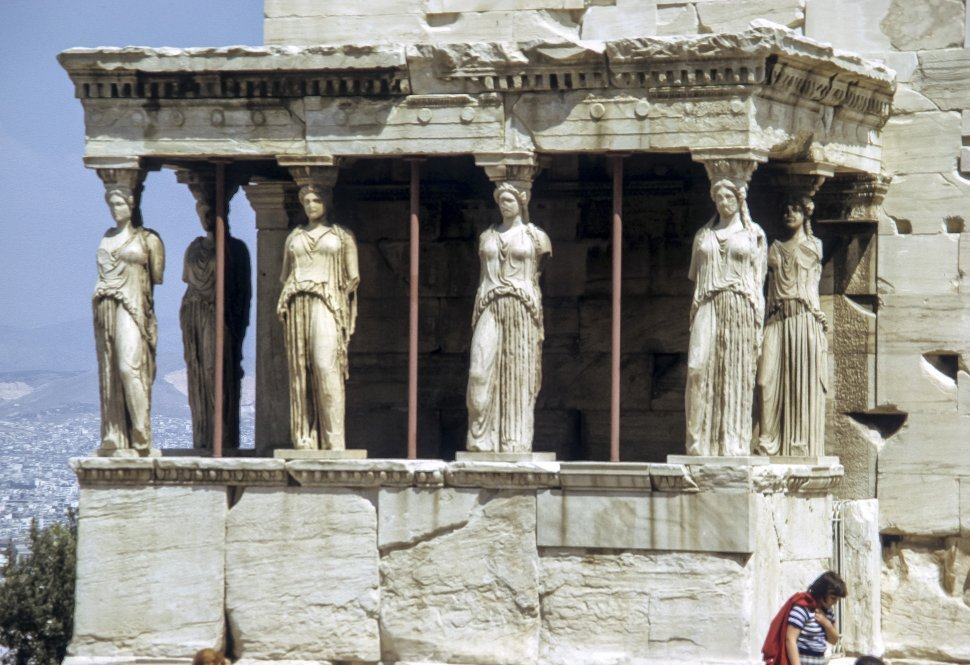 Free image of Woman walking in front of ancient Caryatid Porch of the Erechtheion, Athens, Greece
