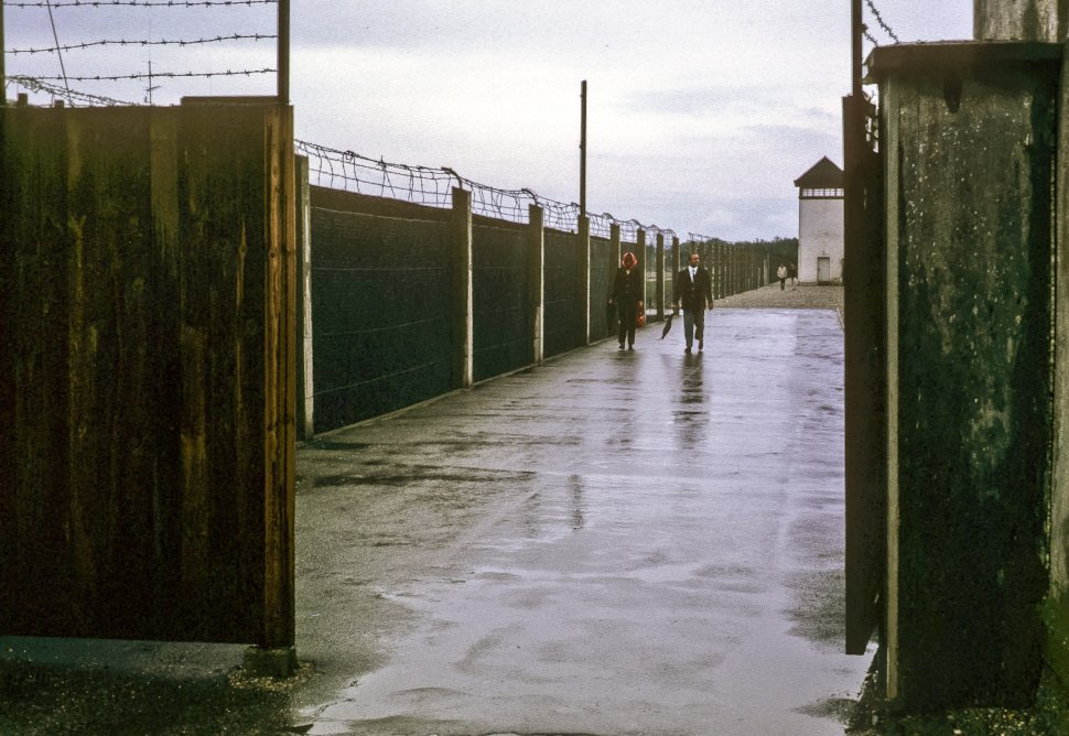 Free image of Two people walking in the rain through a barbed wire covered gate, Germany