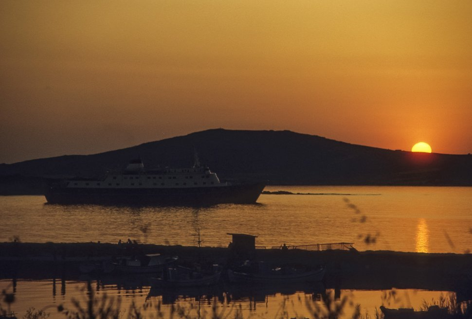 Free image of Cruise ship travelling along the water in the distance, with a scenic sunset.