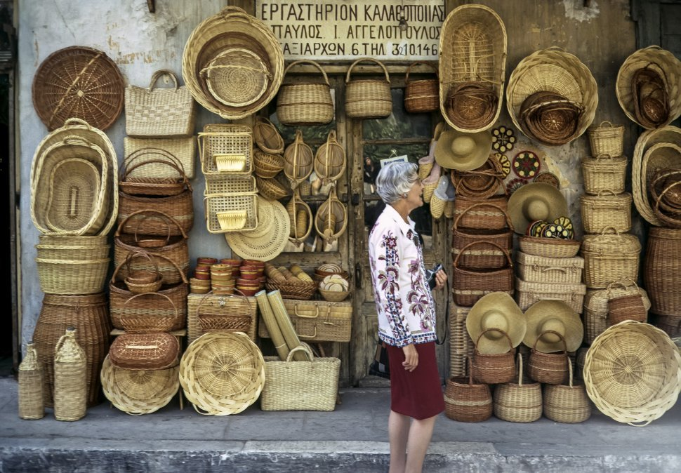 Free image of Woman standing in front of a stall selling woven baskets, Greece