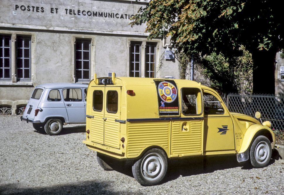 Free image of Yellow vintage truck with colorful signs parked in a lot, Europe
