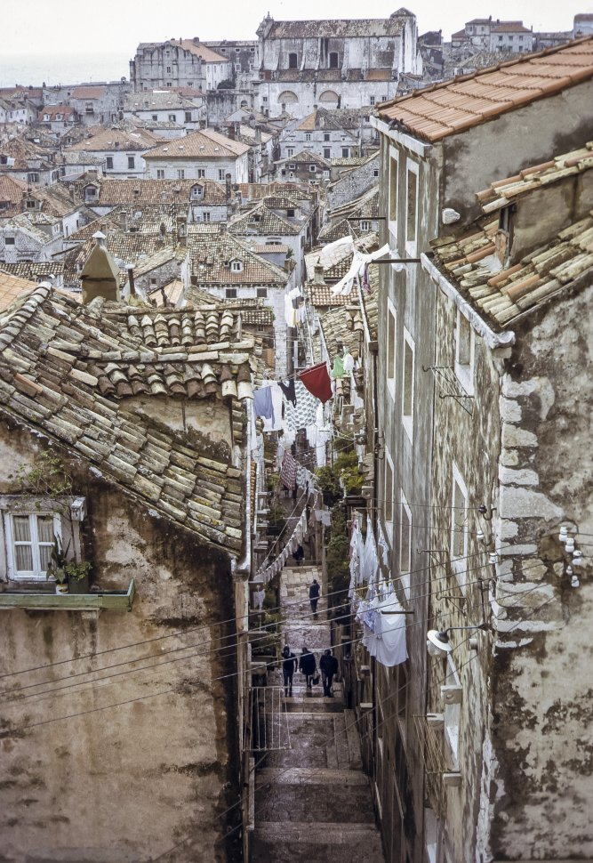 Free image of People walking through a small alley beneath hanging laundry, Europe