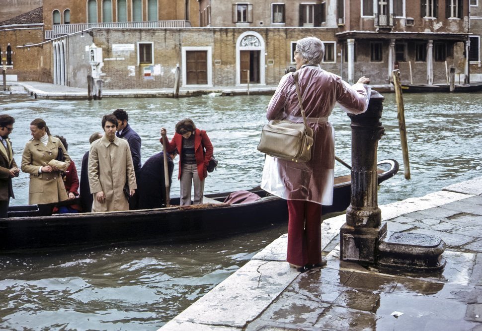 Free image of Woman standing in a raincoat next to a gondola full of people, Venice, Italy.
