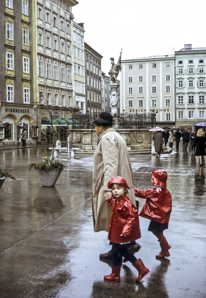 Free image of Mother and her two children walking across a rainy courtyard, Europe