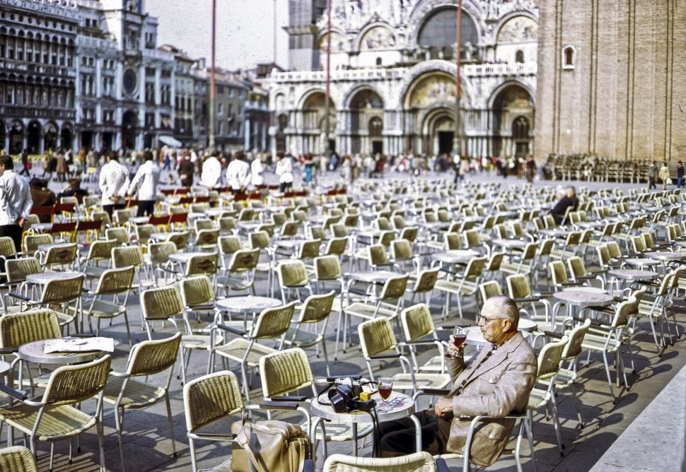 Free image of Man sitting in a large courtyard restaurant, drinking a beer in front of Saint Mark s Basilica, Venice, Italy