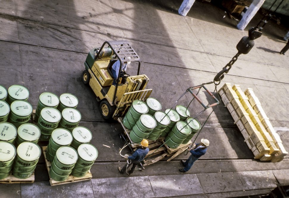 Free image of Workers loading barrels with a forklift onto a crane on a dock, Europe