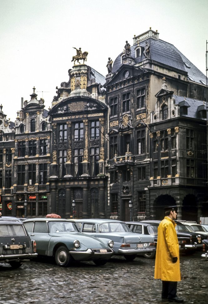 Free image of Traffic guard standing in a parking lot in front of a Maison des Brasseurs, Brussels, Belgum.