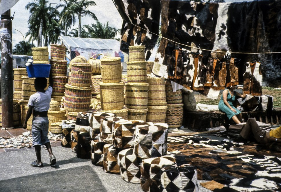 Free image of Child walking throught a marketplace full of baskets and animal skins.