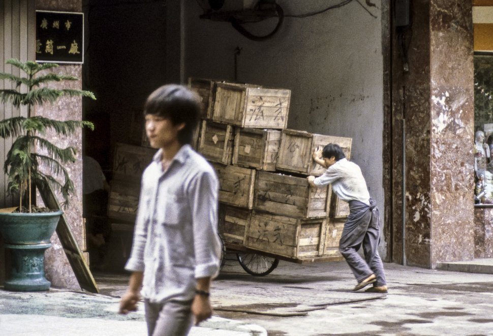 Free image of Man pushing a large cart full of wooden crates, Asia