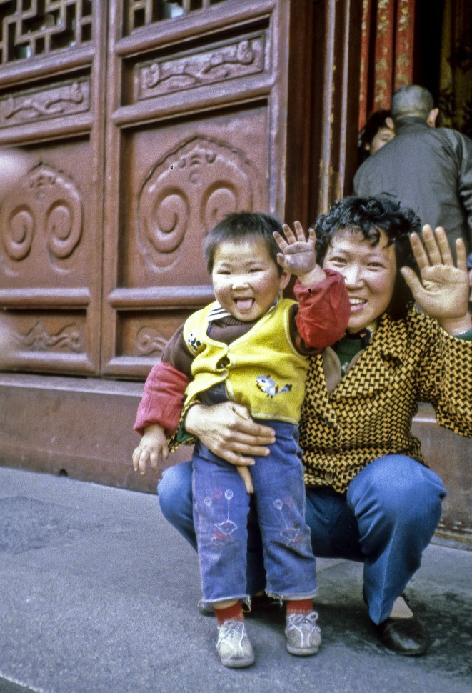 Free image of Mother and child waving at the camera, Asia