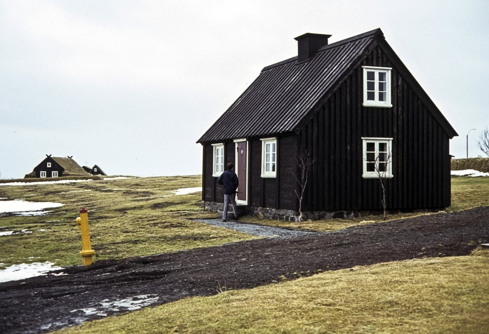 Free image of Woman walking to the entrance of a rural cabin.