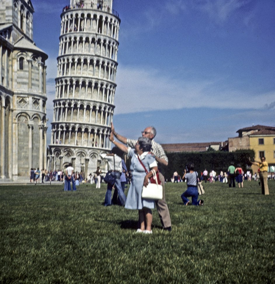 Free image of Couple taking a humorous picture holding up The Leaning Tower of Pisa, Italy