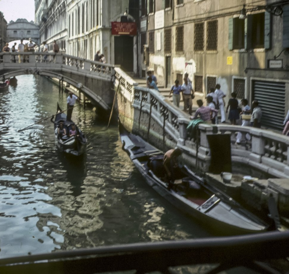Free image of Group of tourists walking past canal and gondolas, Italy